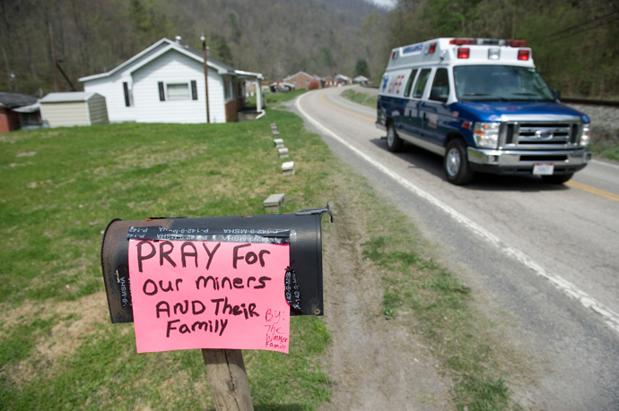 An ambulance drives by a sign praying for miners in Eunice, West Virginia, April 7, 2010, near the Upper Big Branch coal mine owned by Massey Energy Company and operated by Performance Coal Company in Montcoal where an explosion killed 25 miners with 4 still unaccounted for. (AFP Photo / Saul Loeb)