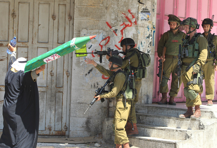 A Palestinian man holding a cardboard model of an M75 rocket confronts Israel soldiers during clashes following a demonstration is support of Gaza after Friday prayers in the West Bank town of Hebron (AFP Photo / Hazem Bader)