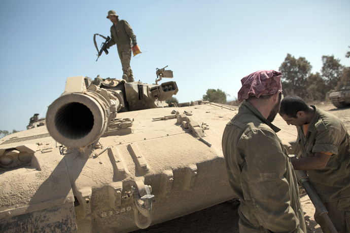 Israeli soldiers works on a Merkava tank at an army deployment point near the Israeli-Gaza border (AFP Photo / Menahem Kahana)