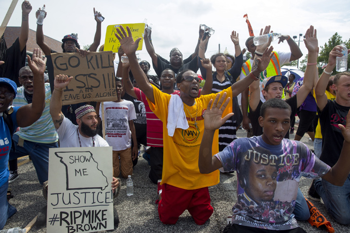 Protesters sit down in the street outside the police department during a protest over the killing of Michael Brown August 30, 2014 in Ferguson, Missouri. (Aaron P. Bernstein / Getty Images / AFP)