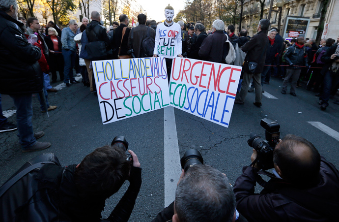 """Photographers take pictures of a man wearing a """"Guy Fawkes"""" mask and holding placards that read, """"Hollande and Valls, you are social breakers"""" (L) and """"Emergency eco sociale"""", during a demonstration against the government's austerity reforms, in Paris November 15, 2014 (Reuters / Gonzalo Fuentes)"""