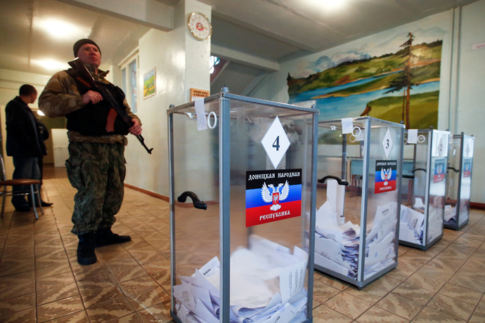 A rebell stands guard during the self-proclaimed Donetsk People's Republic leadership and local parliamentary elections at a polling station, November 2, 2014 (Reuters / Maxim Zmeyev)