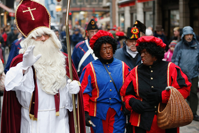 "ARCHIVE PHOTO: Saint Nicholas (L) is followed by his two assistants called ""Zwarte Piet"" (Black Pete) during a traditional parade in central Brussels December 1, 2012 (Reuters / Francois Lenoir)"