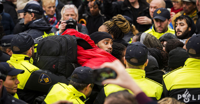 "Police control anti-Black Peter demonstrators in Gouda, on November 15, 2014, as the historic city welcomes Sinterklaas, the Dutch version of Santa Claus (Saint Nicolas) and ""Zwarte Piet"" or Black Peter. Police detaining about 60 protesters (AFP Photo / HO)"