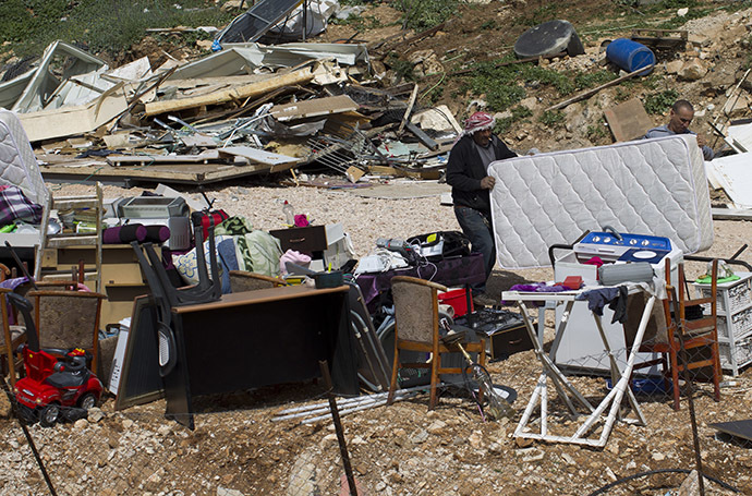Palestinians collect their belongings after their house was demolished by Israeli bulldozers in the Arab east Jerusalem neighbourhood of Beit Hanina on March 19, 2014. (AFP Photo / Ahmad Gharabli)