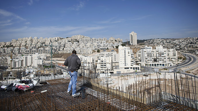 A labourer stands on an apartment building under construction in a Jewish settlement known to Israelis as Har Homa and to Palestinians as Jabal Abu Ghneim, in an area of the West Bank that Israel captured in a 1967 war and annexed to the city of Jerusalem, October 28, 2014. (Reuters/Ronen Zvulun)
