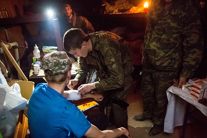 A member of the people's self-defense gives first aid to a person who wounded during a tank attack of the Ukrainian army on Semyonovka village. (RIA Novosti/Andrey Stenin)
