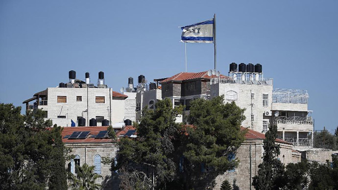 A giant Israeli flag flies over a settlement building situated in the middle of a Palestinian neighbourhood of Al-Tur in East Jerusalem, on November 11, 2014 (AFP Photo/Thomas Coex)