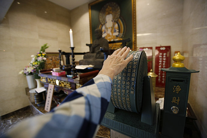 A visitor spins a prayer wheel in front of a Buddhist statue in the lobby of Ryogoku Ryoen, a multi-storey vault-style graveyard equipped with modern tombs that robotically retrieves the correct tombstone or urn based on which identity card is provided, in downtown Tokyo October 27, 2014. (Reuters/Toru Hanai)