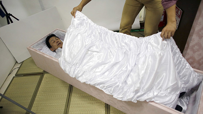 A staff member covers Kazuhiko Kitano with a quilt as he lies in a coffin to test it during an end-life seminar held by Japan's largest retailer Aeon Co in Tokyo October 24, 2014. (Reuters/Toru Hanai)
