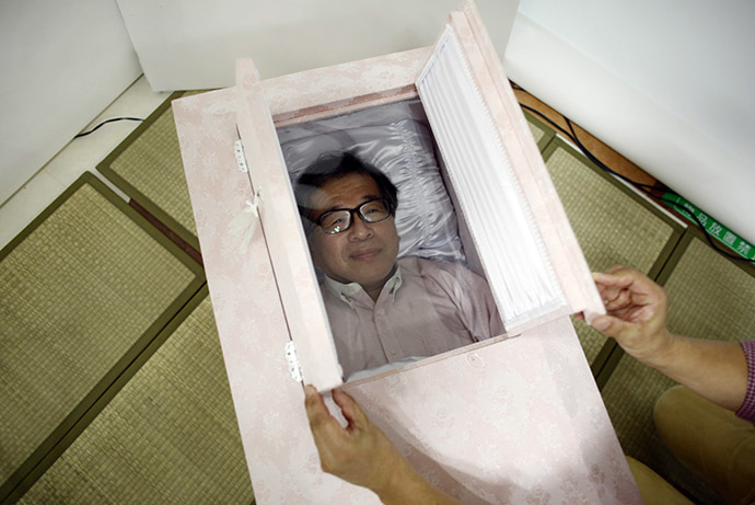 Yoshiya Yoshimura lies in a coffin to try it out during an end-of-life seminar held by Japan's largest retailer Aeon Co in Tokyo October 24, 2014. (Reuters/Toru Hanai)