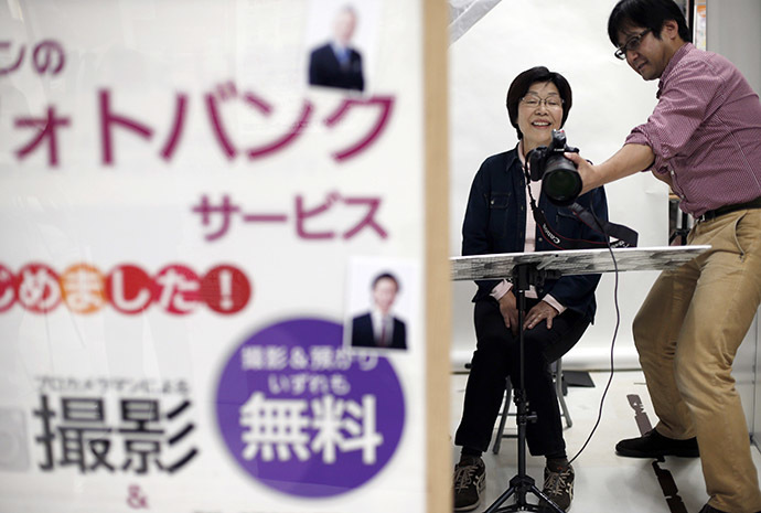 A woman smiles as she is shown her photographic portrait which will be used at her funeral during an end-of-life seminar held by Japan's largest retailer Aeon Co in Tokyo October 24, 2014. (Reuters/Toru Hanai)
