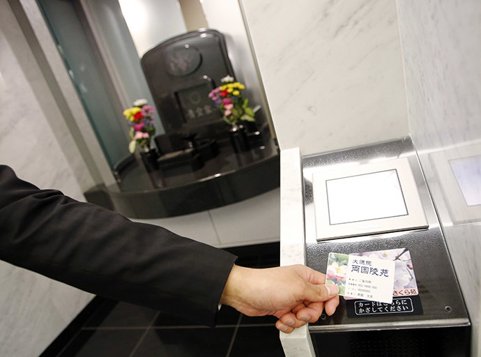 A staff member demonstrates how to use a modern tomb that robotically retrieves the correct tombstone or urn based on which identity card is provided, at Ryogoku Ryoen, a multi-storey vault-style graveyard, in downtown Tokyo October 27, 2014. (Reuters/Toru Hanai)