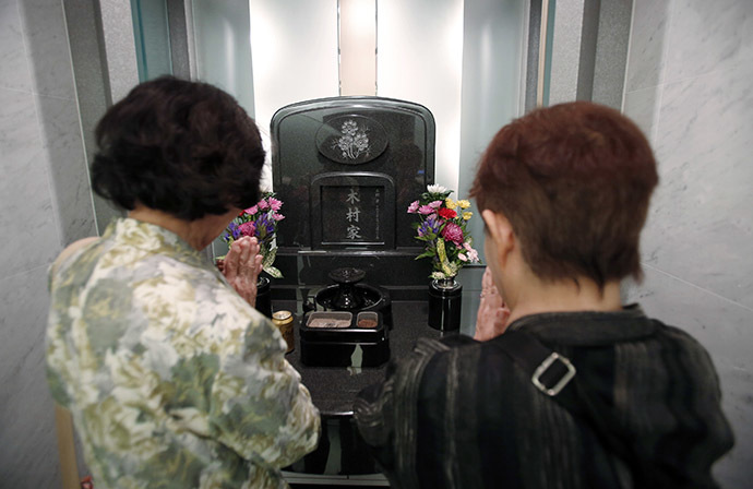 Yukiko Kimura (R) prays for her late husband Mitsugi with Mitsugi's sister Kiyoko Matsuura in front of a modern tomb that robotically retrieves the correct tombstone or urn based on which identity card is provided, at Ryogoku Ryoen, a multi-storey vault-style graveyard, in downtown Tokyo October 27, 2014. (Reuters/Toru Hanai)