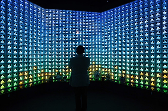 """Junkoh Nagakura prays at the """"Ruriden"""", a cemetery that uses high-powered LED lights to illuminate over 2,000 Buddha statues carved in crystals, in downtown Tokyo October 27, 2014. (Reuters/Toru Hanai)"""