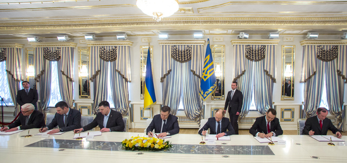 Ukraine's President Viktor Yanukovich (C) signs an EU-mediated peace deal with opposition leaders in Kiev February 21, 2014 (Reuters / Pool)