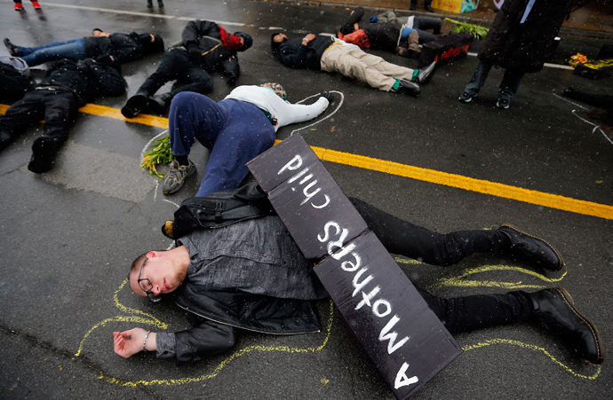 Demonstrators lay on the ground with chalk outlines to represent a mock crime scene during a protest marking the 100th day since the shooting death of Michael Brown in St. Louis, Missouri November 16, 2014 (Reuters / Jim Young)