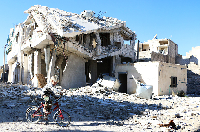 A Syrian boy rides his bike past a destroyed building in the northern Syrian city of Aleppo (AFP Photo / Baraa Al-Halabi)
