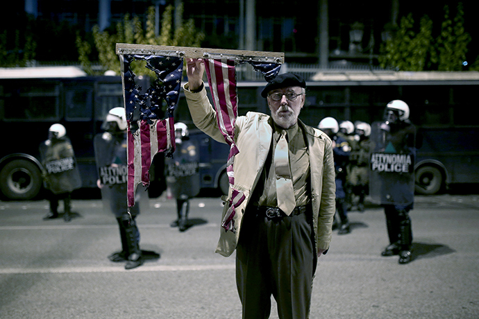 A man holds a burnt US flag in front of the US embassy on November 17, 2014 in the centre of Athens at a march commemorating the 1973 students uprising against the military junta. (AFP Photo / Angelos Tzortzinis)