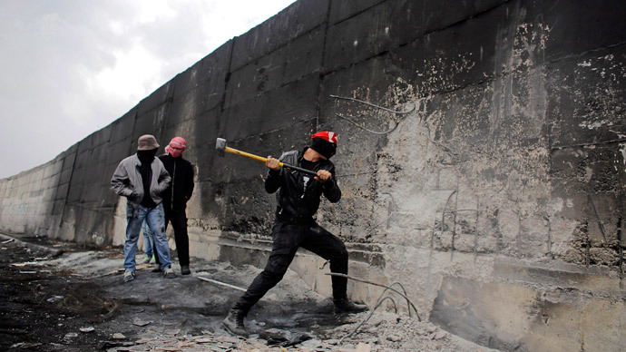 A Palestinian protester tries to hammer a hole through Israel's controversial barrier that separates the West Bank town of Abu Dis from Jerusalem November 17, 2014. (Reuters / Ammar Awad)