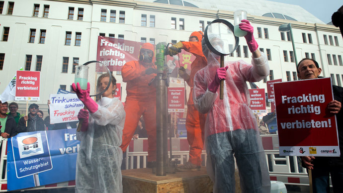 Environmental activists simulate hydraulic fracturing during a protest against fracking in front of the German Ministry of Environment in Berlin on September 30, 2014.(AFP Photo / Bernd Von Jutrczenka)