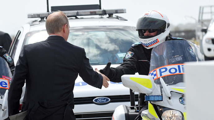 Russia's President Vladimir Putin (L) shaking hands with members of his motorcycle escort at the airport in Brisbane as he leaves the G20 Summit.(AFP Photo / Steve Holland)