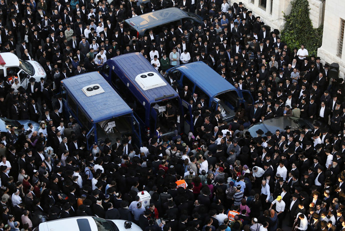 Ultra-Orthodox Jews mourn over the bodies of three of the victims of an attack by two Palestinians on Jewish worshippers killing four Israelis at a synagogue in the Ultra-Orthodox Har Nof neighbourhood in Jerusalem, at the site where the attack took place on November 18, 2014. (AFP Photo/Gali Tibbon)