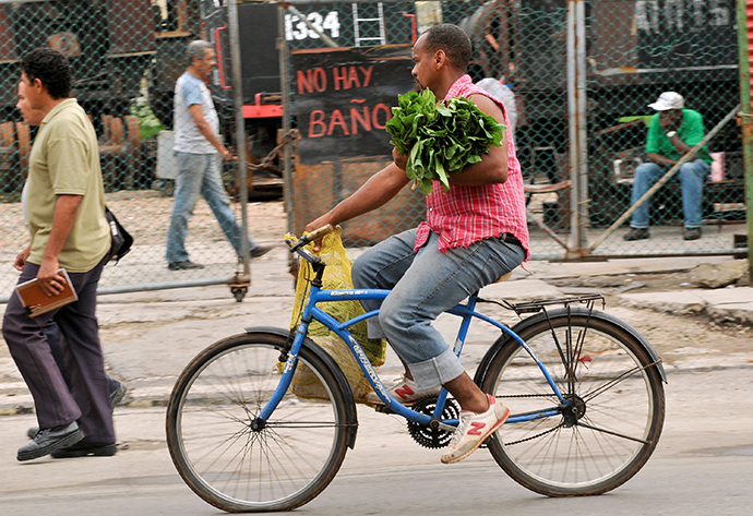 A man carries vegetables as he rides his bike in Havana (AFP Photo / Yamil Lage)