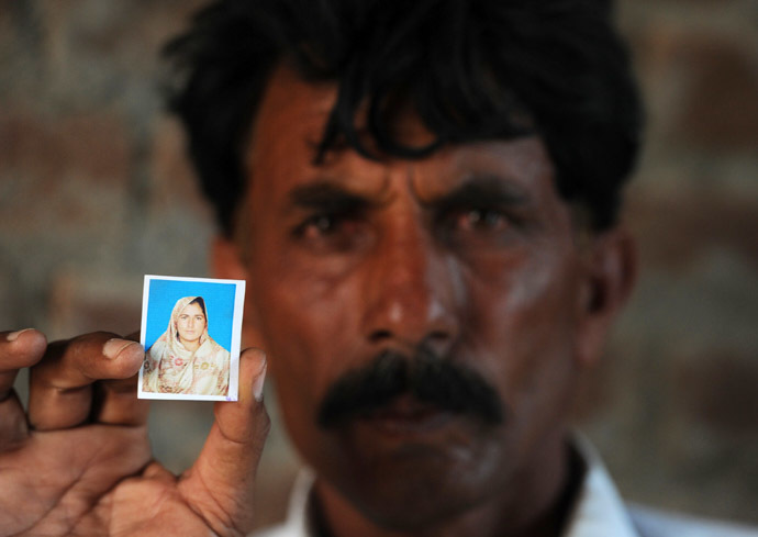 Pakistani resident Mohammad Iqbal poses for a photograph as he holds up an image of his wife Farzana Parveen, who was beaten to death with bricks by her father and other family members for marrying a man of her own choice, in Chak 367 some 40 kms from Faisalabad on May 30, 2014. (AFP Photo)