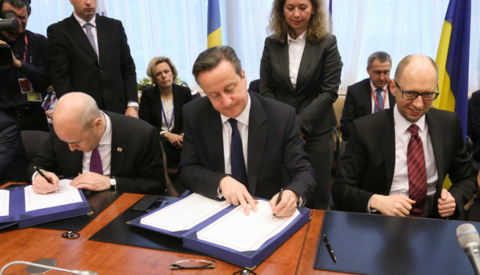 Ukrainian Prime Minister Arseniy Yatsenyuk (R) smiles next to British Prime Minister David Cameron (C) and Swedish Prime Minister Fredrik Reinfeldt (L) as they sign the political provisions of the Association Agreement with Ukraine. (AFP Photo / Pool / Olivier Hoslet)