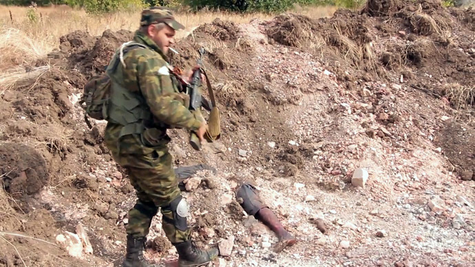 """A Donetsk People's Republic militiaman is at the site of the graves of peaceful residents discovered near Mine 22 """"Kommunar"""" outside Donetsk (stills from video courtesy of the Ruptly international news agency)"""