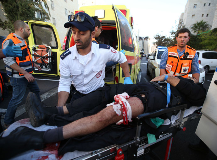 An Israeli man that was injured in an attack, by two Palestinians on Israeli worshippers at a synagogue, is taken to an ambulance by emergency personnel in the ultra-Orthodox Har Nof neighbourhood in Jerusalem on November 18, 2014. (AFP Photo / Miri Tsachie)