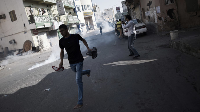 Bahraini protestors run for cover from tear gas fired by riot police during clashes following a rally calling for the boycott of the upcoming parliamentary elections in the Shiite village of Diraz, west of Manama on November 21, 2014.(AFP Photo / Mohammed AL-Shaikh)