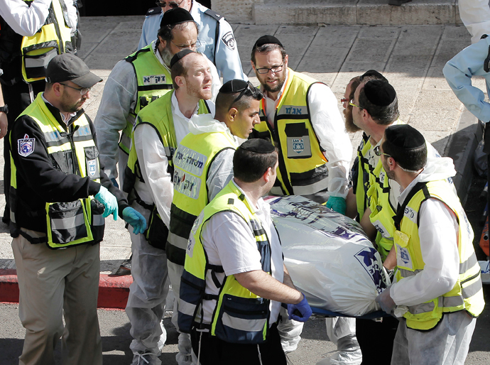Israeli emergency services members carry a body at the scene of an attack, by two Palestinians, on Israeli worshippers at a synagogue in the ultra-Orthodox Har Nof neighbourhood in Jerusalem on November 18, 2014. (AFP Photo / Ahmad Gharabli)