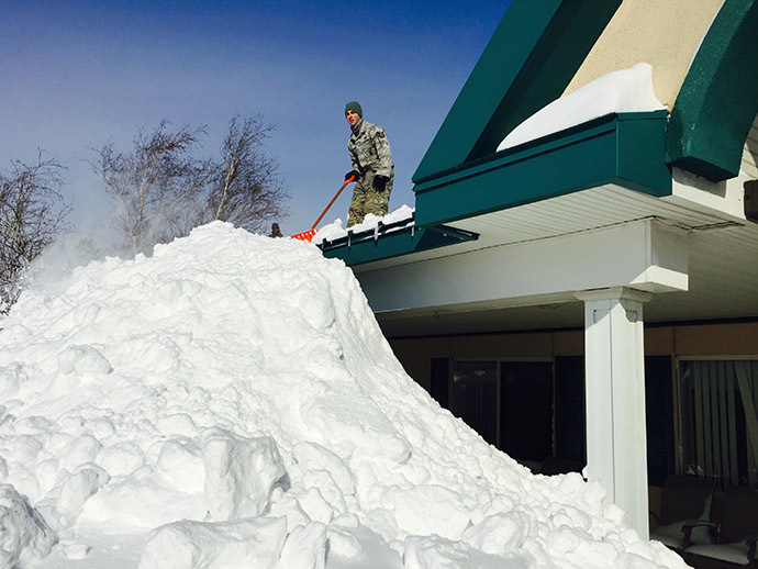 This US National Guard handout photo taken November 19, 2014 shows a New York Air National Guard Airman from the 107th Airlift Wing based in Niagara Falls, New York assisting in snow removal efforts from the roof of the Eden Heights Assisted Living Facility in West Seneca, New York. (AFP Photo /Handout / US National Guard / Maj. Mark Frank)