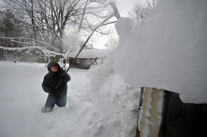 Mike Ostrander tries to remove some of the five feet of snow from his roof on November 20, 2014 in the Lakeview neighborhood of Buffalo, New York. (AFP Photo/John Normile)