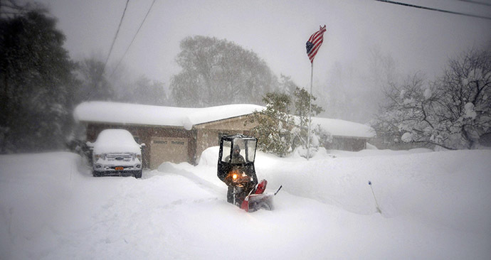 BUFFALO, NY - NOVEMBER 20: Norbert Schnorr attempts to remove some of the five feet of snow from a driveway on November 20, 2014 in the suburb of Lakeview, Buffalo, New York. (AFP Photo/John Normile)