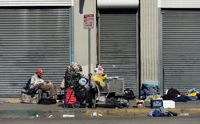 Homeless people rest on a public sidewalk in downtown skid row area of Los Angeles, California. (AFP Photo / Kevork Djansezian)