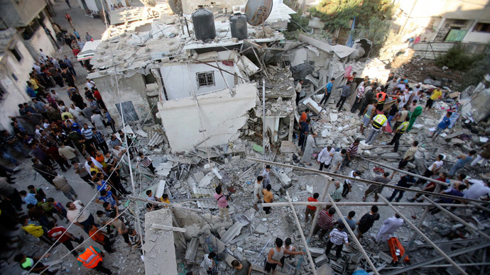 Palestinian rescue workers and onlookers stand on the rubble of a house, which witnesses said was destroyed by an Israeli air strike, as they search for casualties in Rafah, southern Gaza.(Reuters / Ibraheem Abu Mustaf)
