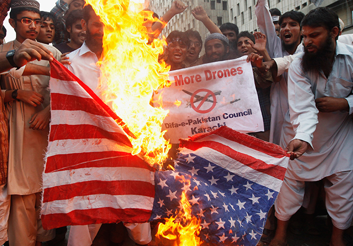 Supporters of the Difa-e-Pakistan Council, an Islamic organization, burn a U.S. flag as they shout slogans during a protest against U.S. drone attacks in the Pakistani tribal region, in Karachi November 8, 2013 (Reuters / Athar Hussain)