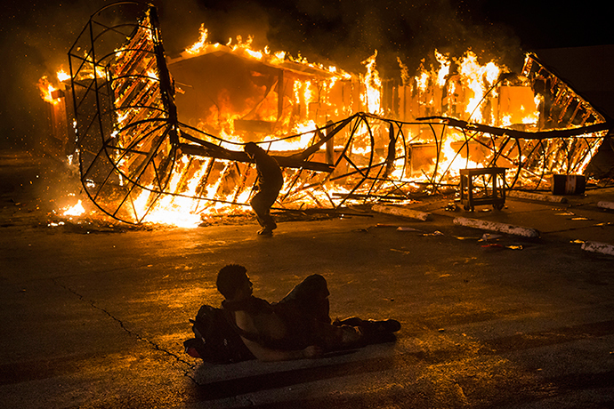 A resident, lying shirtless, keeps warm as another approaches the blazing skeleton of Juanita's Fashions R Boutique after it was burned to the ground in Ferguson, Missouri early morning November 25, 2014 (Reuters / Adrees Latif)