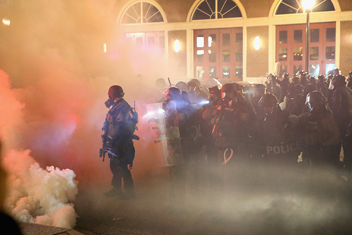 Police guard the Ferguson police department as rioting erupts following the grand jury announcement in the Michael Brown case on November 24, 2014 in Ferguson, Missouri (AFP Photo / Scott Olson)