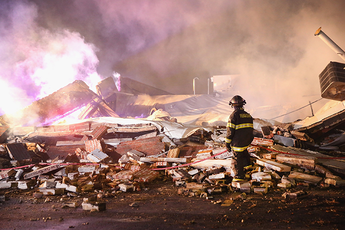 A Ferguson firefighter surveys damage to a strip mall that was set on fire when rioting erupted following the grand jury announcement in the Michael Brown case on November 25, 2014 in Ferguson, Missouri (AFP Photo / Scott Olson)