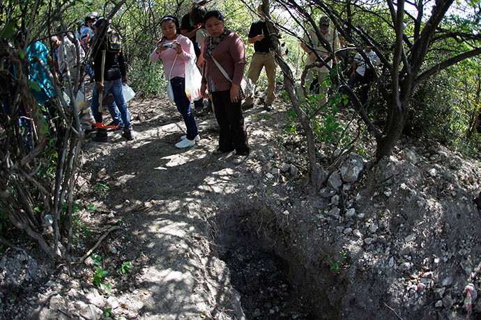 People with missing relatives stand around mass graves discovered in October, in La Joya, on the outskirts of Iguala, Guerrero state, November 21, 2014 (Reuters / Jorge Dan Lopez)