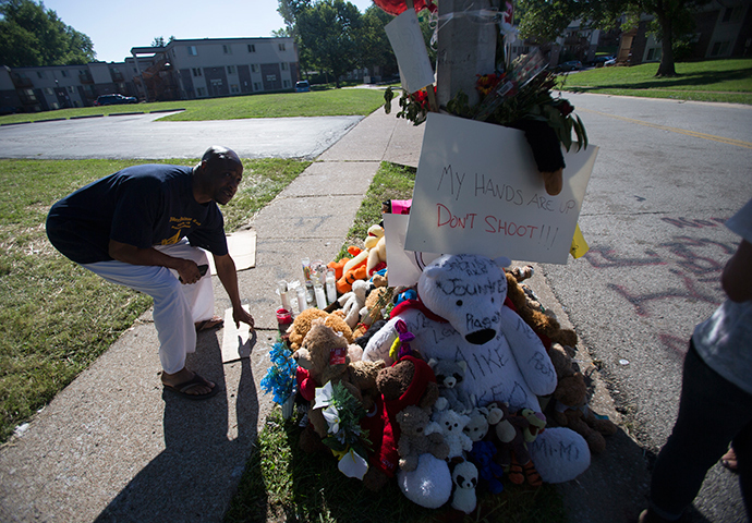 A man picks up a sign that fell from a makeshift memorial near where black teenager Michael Brown was shot to death by police over the weekend in Ferguson, Missouri August 12, 2014 (Reuters / Mario Anzuoni)