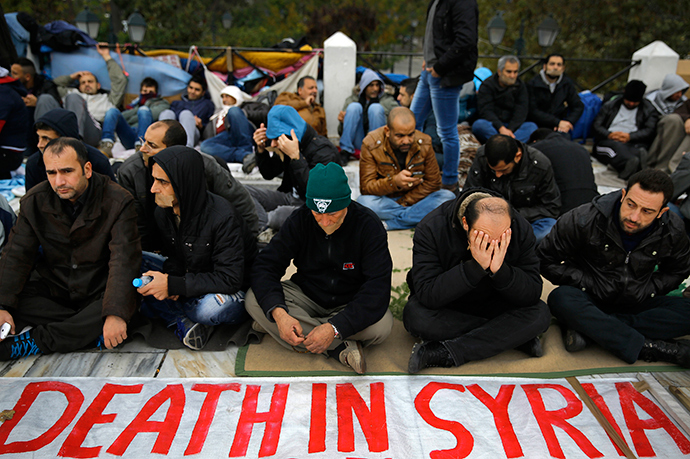 Syrian refugees, some with tape across their mouths, sit with a banner during a protest for a sixth consecutive day in central Athens November 24, 2014 (Reuters / Yannis Behrakis)