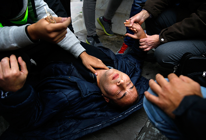 A Syrian refugee is tended to by fellow refugees after collapsing during a protest on its sixth consecutive day in central Athens November 24, 2014 (Reuters / Yannis Behrakis)