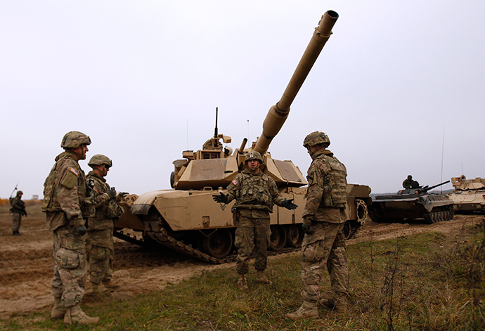 Members of the U.S. 1st Brigade Combat Team, 1st Cavalry Division discuss in front of an Abrams tank during a joint military exercise with Poland's 1st Mechanized Battalion of the 7th Coastal Defence Brigade near Drawsko-Pomorskie November 13, 2014 (Reuters / Kacper Pempel)