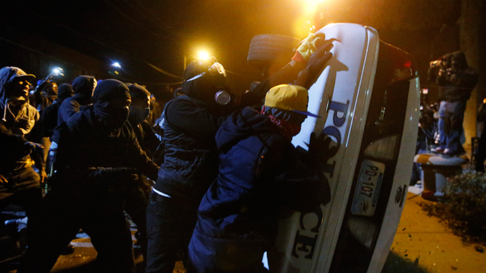 Protesters try to flip over a Ferguson police car, in Ferguson, Missouri, November 25, 2014 (Reuters / Jim Young)