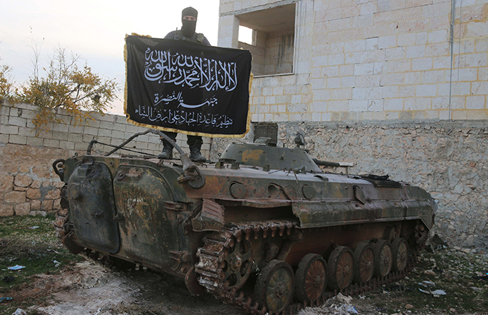 A member of al Qaeda's Nusra Front poses with the Nusra flag on top of an infantry fighting vehicle at the frontline near al-Zahra village, north of Aleppo city, November 25, 2014 (Reuters / Abdalrhman Ismail)
